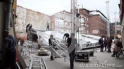 露天阶段,人装配用灰色不透明的篷布包括它 股票录像