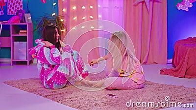 风趣的朋友们两个穿着滑稽睡衣的漂亮女士,一个是独角兽,享受着坐在一起的时光 影视素材