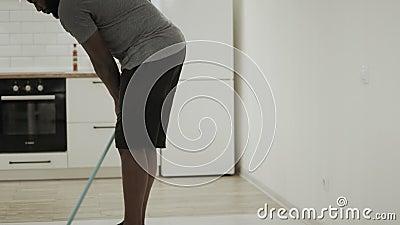 黑人在厨房的清洁地板有拖把的 在袜子的严肃的人洗涤物地板 影视素材