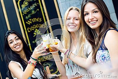 Друзья принимая питье на террасе
