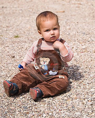1 year old baby sitting on pebble