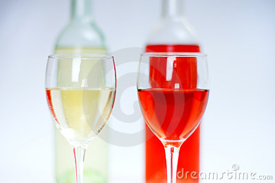 2 glasses of white and rose wine with bottles and white background
