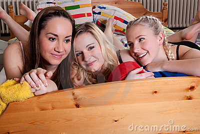 3 adorable girlfriends cuddling in a bed