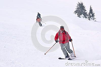 3 esquiadores que funcionam para baixo do monte