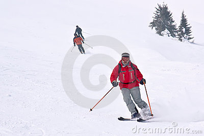 3 skiers running down from hill