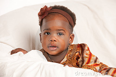 3 year old African American girl sit on bed