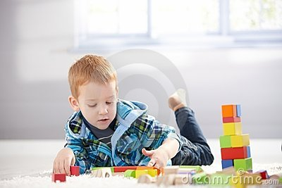3 year old playing with cubes on floor