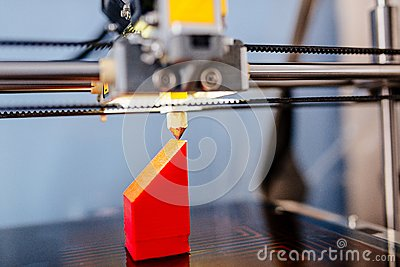 3d printer printing red plastic component Stock Photo
