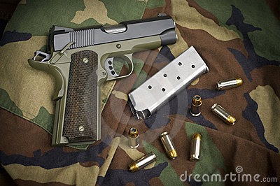 45 Firearm Pistol Clip And Hand Gun on Camouflage