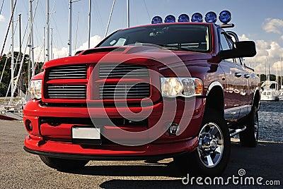 4x4 red pickup in harbor