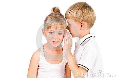5-7 years old boy whispering to girl