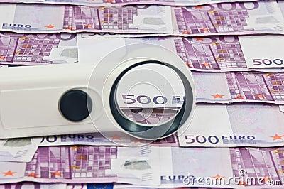 500 euro bills and magnifying glass vista