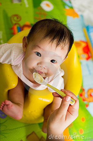6 month old Asian baby girl being fed cereal
