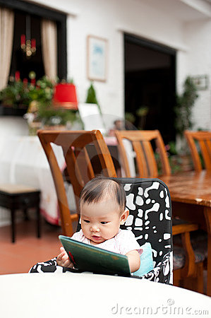 7 month old Asian baby girl reading lunch menu