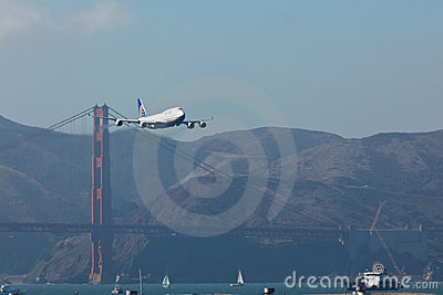 747 jet over Golden Gate Bridge in San Francisco Editorial Stock Photo