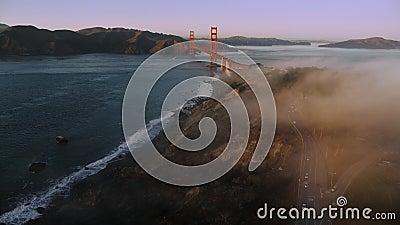 Aéreo sobre la bahía de San Francisco: orilla nigosa rocosa que se acerca al puente Golden Gate al atardecer almacen de metraje de vídeo