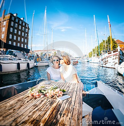 Free A Beautiful Female Lesbian Couple In White Dresses On A Boat, A Royalty Free Stock Image - 111830516