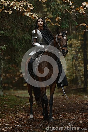 Free A Beautiful Warrior Girl With A Sword Wearing Chainmail And Armor Riding A Horse In A Mysterious Forest. Royalty Free Stock Images - 116646409
