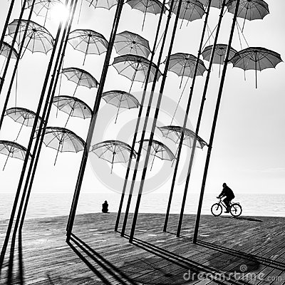 Free A Bicyclist And A Girl Under The Umbrellas Royalty Free Stock Photography - 108506037