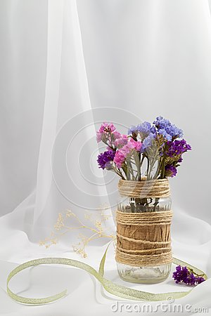 Free A Bouquet Of Dried Pink, Blue And Purple Flowers In A Glass Jar Decorated Stock Images - 113281814