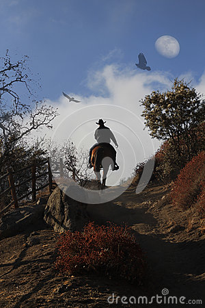 Free A Cowboy Riding His Horse Up A Hill. Royalty Free Stock Images - 36589239