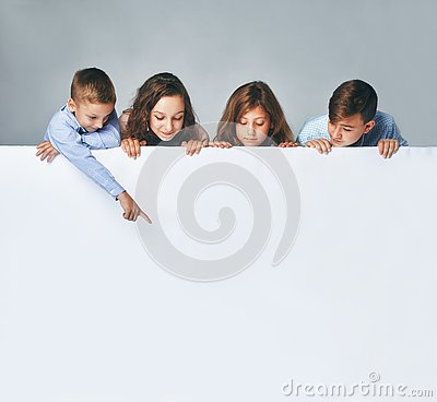 Free A Four Children Holding A Big Billboard, Looking Down On It. Stock Images - 127277264