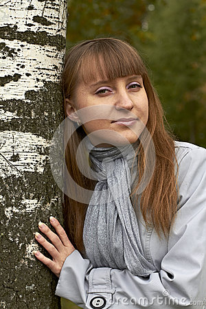 Free A Girl Put Her Arms Around The Trunk Of A Birch T Tree With Golden Hair Wearing Glasses In A Bright Scarf Cool Summer Slight Smile Stock Image - 27281311