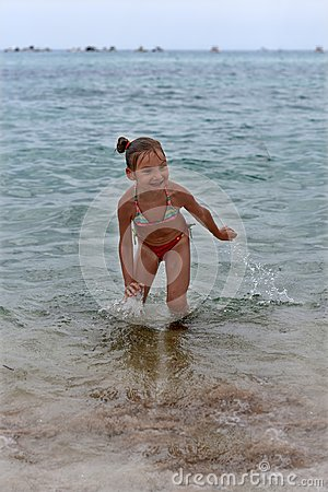 Free A Laughing Little Girl Standing In The Sea Waves Stock Images - 102610104