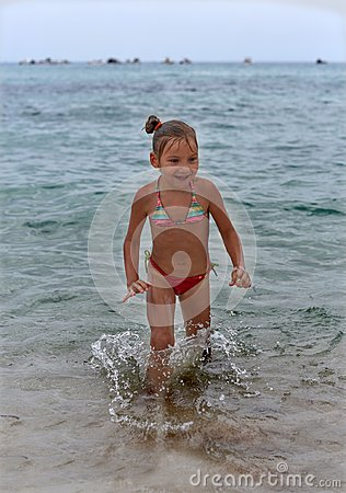 Free A Laughing Little Girl Standing In The Sea Waves Stock Photo - 102610290