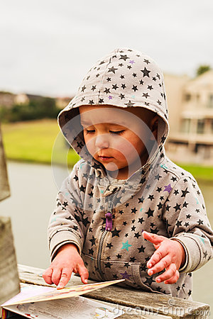 Free A Little Baby Girl Examines A Book Royalty Free Stock Images - 49187549