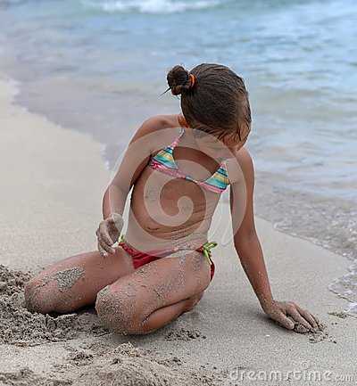 Free A Little Girl Playing With Sand On The Beach Royalty Free Stock Image - 102610246