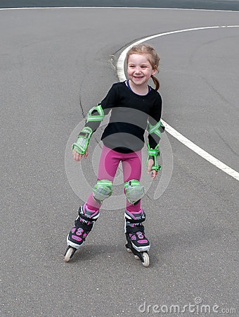 Free A Little Smiling Girl Practicing Inline (roller) Skating In The Outdoor Stadium Royalty Free Stock Photo - 73366305