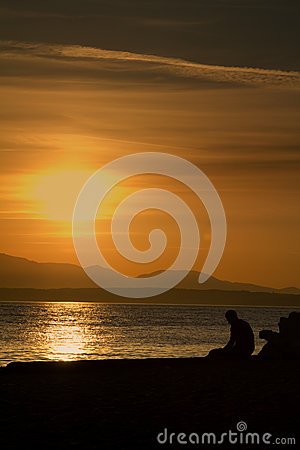 Free A Lonely Sad Man Sitting Alone At The Beach During Sunset. Shot At The Golden Gardens Park In Seattle, Washington. Stock Images - 82221314