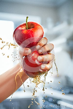 Free A Male Hand Squeezes Fresh Juice. Pure Apple Juice Pouring Out From Fruit Into Glass Stock Images - 106399334