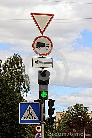 Free A Post With Traffic Signs And A Traffic Light At A Crossroads Stock Photo - 96140780