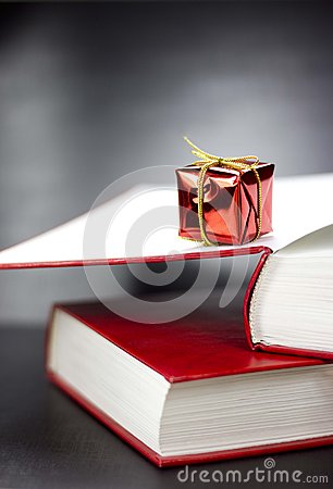 Free A Present Lying On Two Books On A Black Background Stock Photo - 25173300