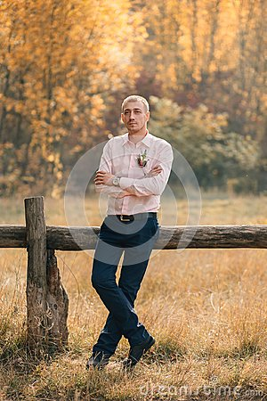 Free A Stylish, Adult, Successful Man Stands On The Background Of A Wooden Fence. The Guy Is Dressed In A Pink Shirt And Blue Stock Images - 122071534