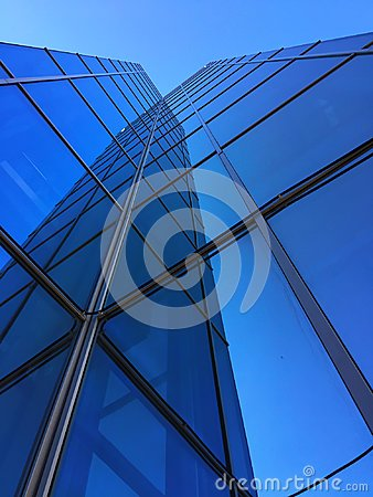 Free A Tall Glass Building Against A Blue Sky With Reflection Stock Images - 108838904