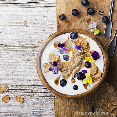 Free A Wooden Bowl With Homemade Breakfast: Yoghurt, Whole Grains, Blueberries, Edible Flowers Of A Garden Viola On A Simple Stock Photography - 96206112