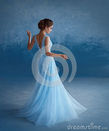 Free A Young Blonde Girl Is Spinning In A Luxurious Blue Dress With An Open Back. The Background Is A Sky-blue Wall Stock Images - 116978424