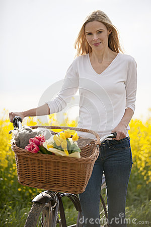 Free A Young Woman Pushing A Bicycle Next To A Rape Seed Field In Flower Royalty Free Stock Photography - 67263977