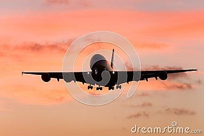 A380 lijnvliegtuig naderbij komen die bij zonsondergang landt