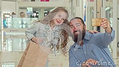 Aanbiddelijk meisje die selfies met haar vader bij het winkelcomplex nemen stock footage