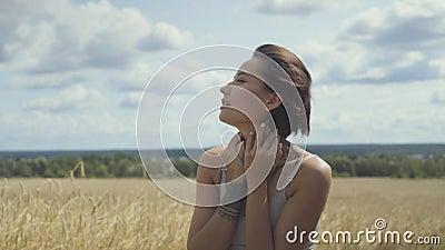 Aanbiddelijke vrouw die bodysuit met kort haar dragen die door het tarwegebied lopen die rond eruit zien Zeker onbezorgd meisje stock videobeelden