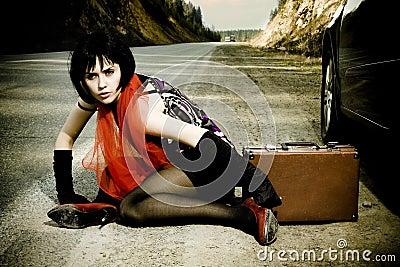 Aantrekkelijk meisje met de koffer dichtbij de auto