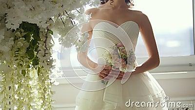 Aantrekkelijk model in huwelijkskleding met bruid` s boeket stock footage