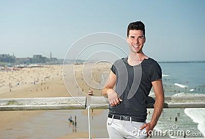 Aantrekkelijke jonge mens die bij de kust glimlachen