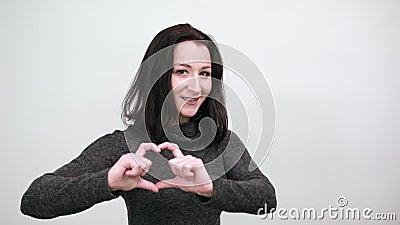 Aantrekkelijke jonge vrouw die vorm van het hart ziet, glimlacht Lifestyle-concept stock videobeelden