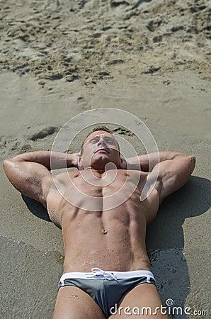 Aantrekkelijke spier jonge mens die op het strand, grote copyspace rusten