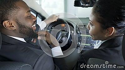 Aantrekkelijke vrouw die haar collega overreden om machinaties te begaan, die in auto zitten stock video